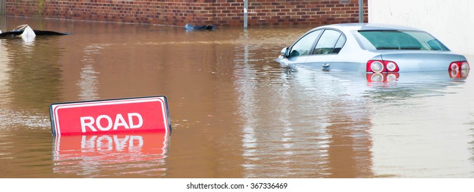 UNITED KINGDOM, YORK, 29th December 2015. Road closed sign because of flooding with a car partly submerged in the flood water.