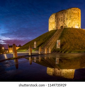 UNITED KINGDOM, YORK - DECEMBER 18, 2018. Cliffords Tower in York is a famous landmark. Shot was made in the evening after rain to capture the reflection in water.