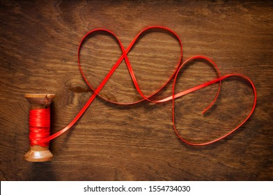united red ribbon hearts  on wood background ,  love concept