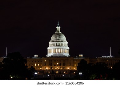 United State Capitol in Washington DC taken by night with its lights and a partially clouded sky.