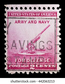 UNITED STATES OF AMERICA - CIRCA 1940: A used postage stamp printed in United States shows a cannon on red background and the words Army and Navy for defense program, circa 1940