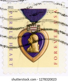 UNITED STATES OF AMERICA - CIRCA 2011: forever post stamp printed in USA (US) shows purple heart medal on ribbon; honors veterans sacrifices served in US military; purple gold; circa 2011