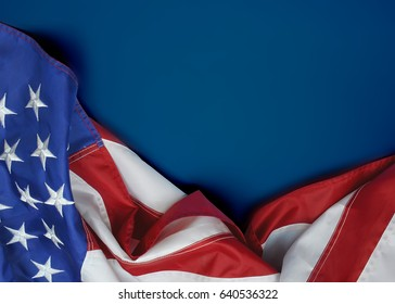A United States of America flag draped as a border with a blue background and copy space