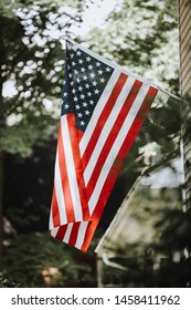 United States of America Flag Flying in Front of House With Beautiful Greenery Behind USA Bokeh