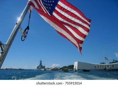 United States of America flag flying above the USS Arizona Memorial in Pearl Harbor on the island of Oahu.