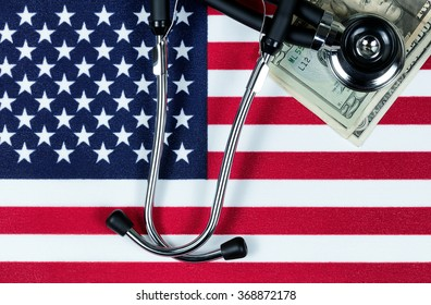 United States of America flag with stethoscope and paper money currency. USA financial health concept. Overhead view in horizontal layout.