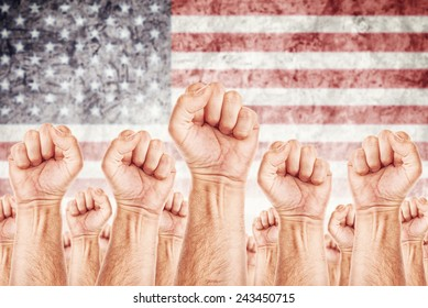 United States of America Labor movement, workers union strike concept with male fists raised in the air fighting for their rights, American national flag in out of focus background.