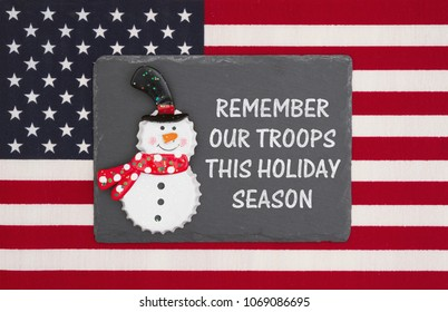 United States of America military holiday message, United States of America flag with a black chalkboard and snowman with text Remember our troops this holiday season