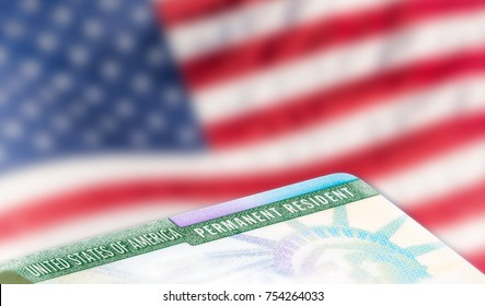 United States of America permanent resident card, green card, with US flag in the background. Legal immigration concept. Closeup with shallow depth of field.