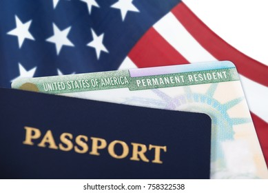 United States of America permanent resident card, green card, displayed with a US flag in the background and a passport in the foreground. Immigration concept. Close up with shallow depth of field.