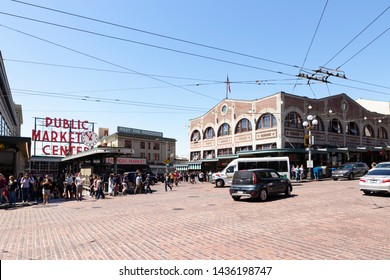 United States of America, USA, Seattle, Washington, Pike Street and 1st Avenue, May 10th 2019. View from the crossing on Pike Place Market with the red public market sign.