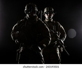 United States Army rangers with assault rifles on dark background