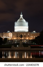 The United States Capitol building at night with scaffolding surrounding the dome as it undergoes restoration