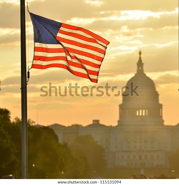 United States Capitol building silhouette and US flag at sunrise - Washington DC