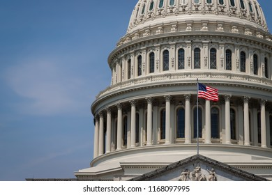 The United States capitol building in Washington DC on a summer day with its flag waving in the wind..