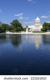 United States Capitol, Government in Washington, D.C., United States of America. Blue Sky behind with building reflecting in the reflection pool.