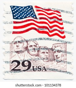 UNITED STATES - CIRCA 1991: A postage stamp printed in the United States, features waving US flag and Mount Rushmore National Memorial, circa 1991