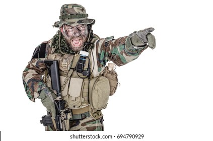 United States Commando half length studio shot. Mouth opened, soldier yelling, emitting intiminate formidable frightening scream pointing finger target and giving attack direction to subordinates