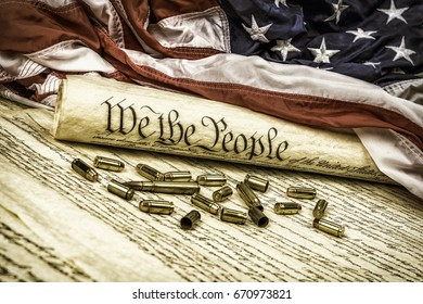 The United States Constitution rolled up on an American flag with bullets scattered about symbolizing the second amendment.