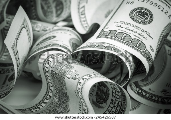 United States dollars. Pile of hundred USD banknotes. Green toned photo with selective focus