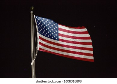 United States flag blowing in the wind at night