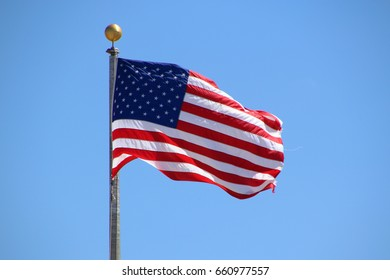 United States Flag Blowing in the Wind with Blue Sky Background