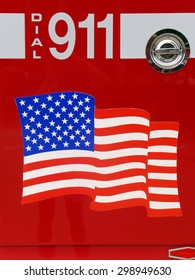 United States flag and Dial 911 sign on the side of a fire truck