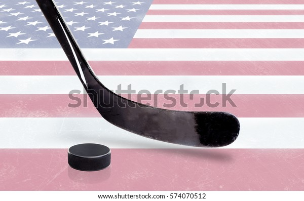 United States flag embedded on ice hockey rink surface with stick and puck. Low angle view and copy space.