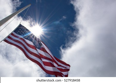 United States flag at half mast, seen from below with the sun behind