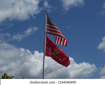 United States Flag and Marine Corps flag against a blue sky with white clouds