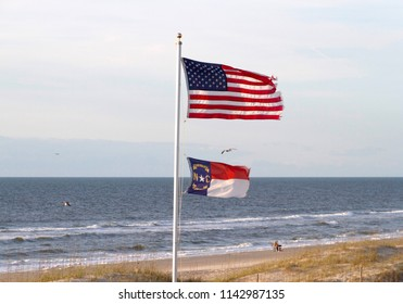 The United States Flag and the North Carolina State Flag fly together on a beach flagpole by the ocean with the shining sea behind them on a sunny day