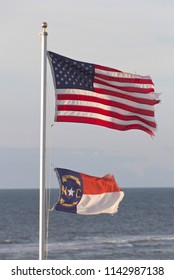 The United States Flag and the North Carolina State Flag fly together on a flagpole with the shining sea behind them on a sunny day