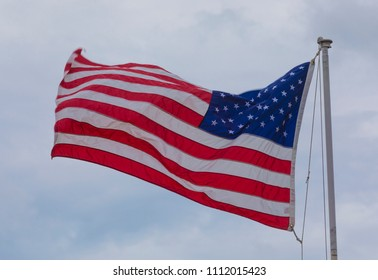 United States flag on a pole with a stiff breeze behind