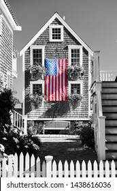 United States flag at suburban neighborhood. Provincetown, Cape Cod, Massachusetts, USA. Black and white image.