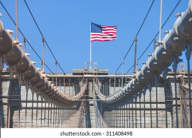 United States Flag at top of Brooklyn Bridge. There is a deep blue sky on background, on foreground there are all the wires of the bridge. Patriotism concept.
