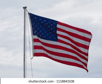 United States flag waving on a pole with clouds behind