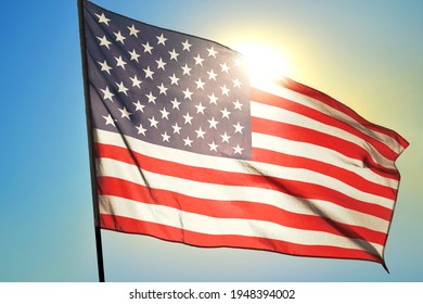 United States flag waving on the wind in front of sun