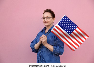 United States flag. Woman holding American flag. Nice portrait of middle aged lady 40 50 years old holding a large USA flag over pink wall background on the street outdoors.