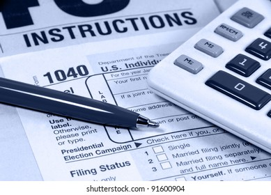 United States Income Tax 1040 Form and Instruction Sheet, Calculator, and Pen.