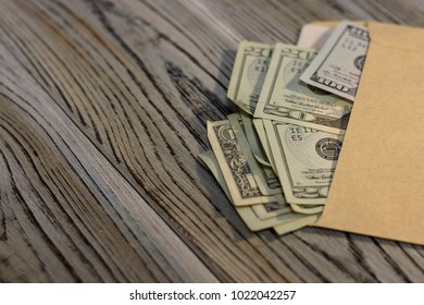 United States money in an envelope on the table. Rough boards background. Money concept. Closeup