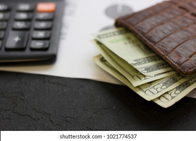 United States money in a vallet on the table next to calculator. USA dollars. Money concept. Closeup