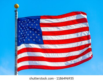United States National Flag waving in a beautiful blue clear sky day