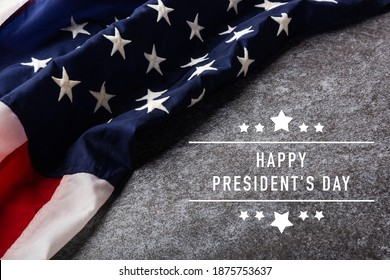 "United States National Holidays. American or USA Flag with ""HAPPY PRESIDENT'S DAY"" text on cement background, President Day concept"