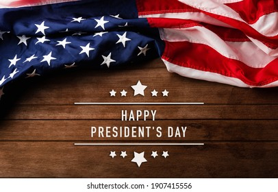 "United States National Holidays. American or USA Flag with ""HAPPY PRESIDENT'S DAY"" text on wooden ement background, President Day concept"