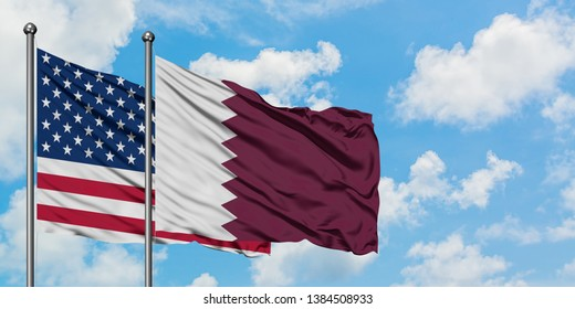 United States and Qatar flag waving in the wind against white cloudy blue sky together. Diplomacy concept, international relations.