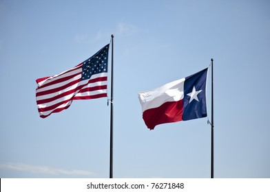 The United States and Texas flags flying high together against a blue lightly cloudy sky.