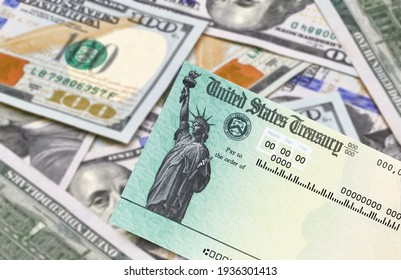 United States Treasury check with US currency and covid mask. Coronavirus economic impact stimulus payments or IRS tax refund.