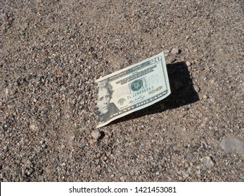 United States Twenty Dollar Bill Partially Hidden Under The Ground In The Morning Sunlight