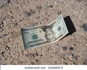 United States Twenty Dollar Bill Laying On The Ground In The Morning Sunlight