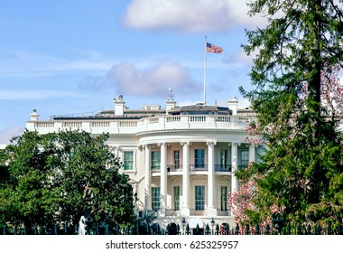 The United States White House on a beautiful sunny afternoon with a red, white, and blue flag on the roof and bright blue sky.